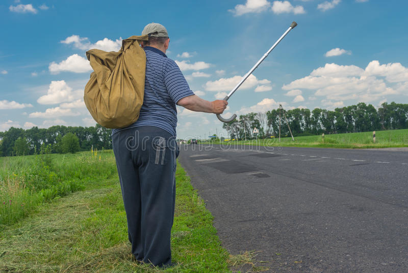 Man with sack standing on a roadside holding walking stick up royalty free stock images