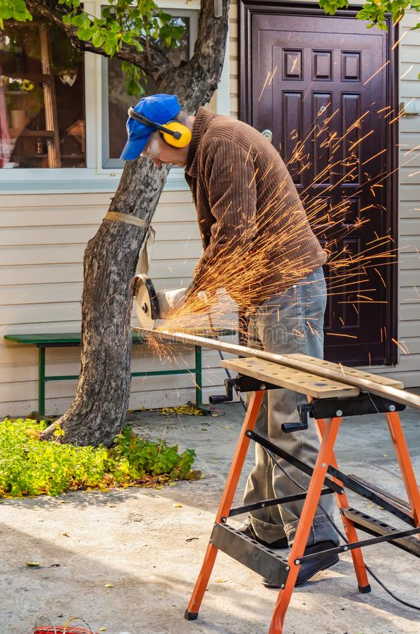 A man in the safety glasses and yellow ear protectors and a brown jacket cuts metal using the big white angle grinder stock photo
