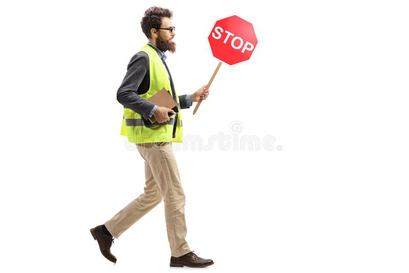 Man in a safety vest holding a stop traffic sign walking royalty free stock photos