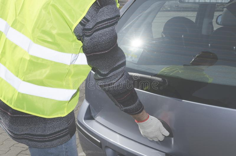 Man in a safety vest is opening boot in his car royalty free stock photo