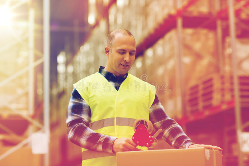 Man in safety vest packing box at warehouse stock image