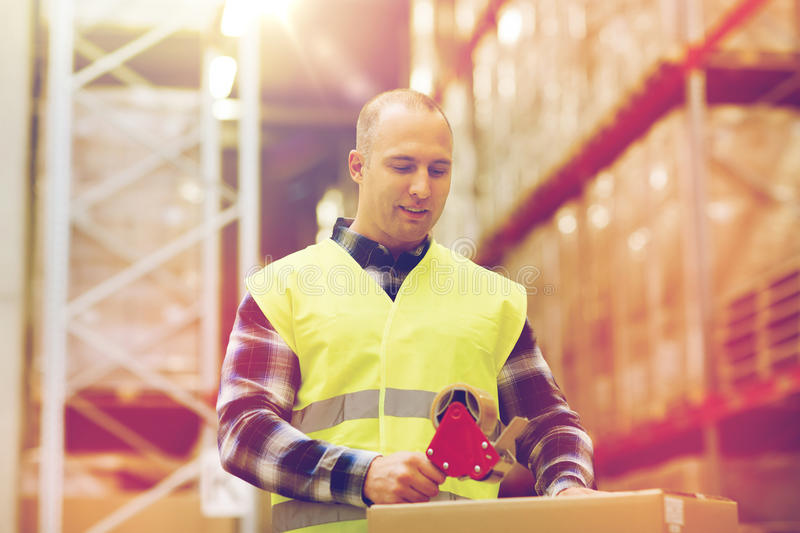 Man in safety vest packing box at warehouse stock photos