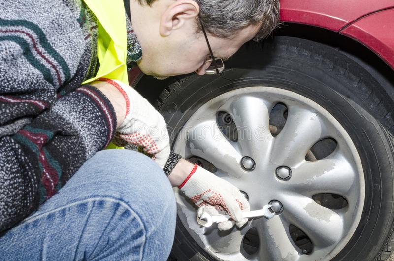 A man in a safety vest repairs a car royalty free stock photo