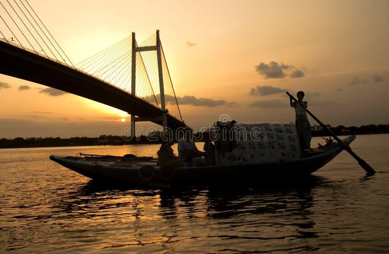 Man sailing boat at sunset near a bridge. At Kolkata, India royalty free stock photo