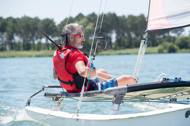 Man sailing with sails out on sunny day stock images