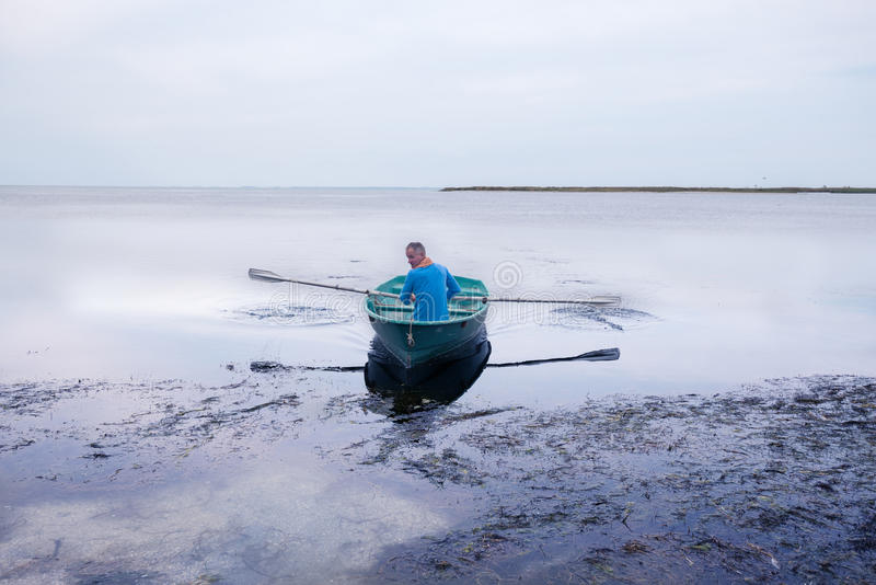 Man sailing on a small rowing boat along the sea coast. At the quiet evening stock photo