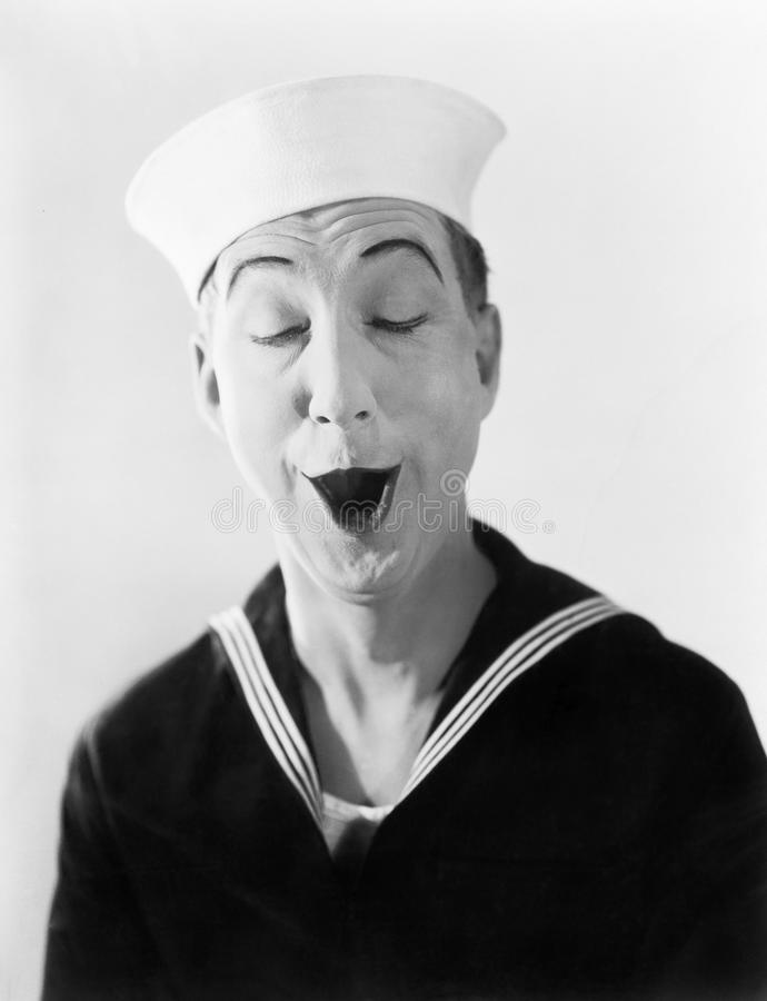 Man in sailor hat and uniform making a silly pantomime face. (All persons depicted are no longer living and no estate exists. Supplier grants that there will be royalty free stock image