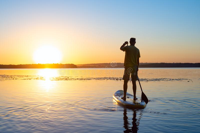 Man sails on a SUP board in a large river during sunrise royalty free stock photography