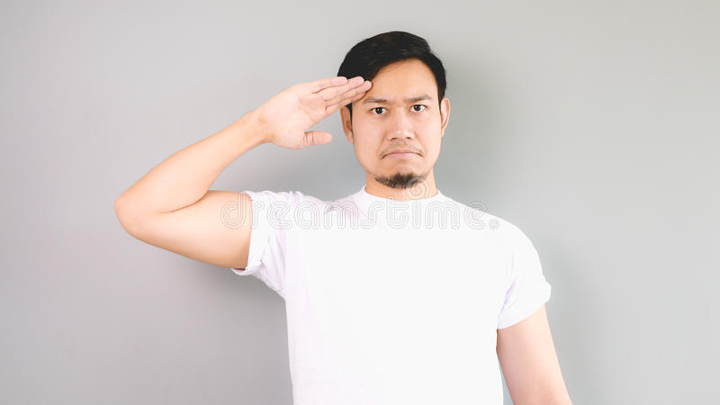A man in salute pose and serious face. royalty free stock photos