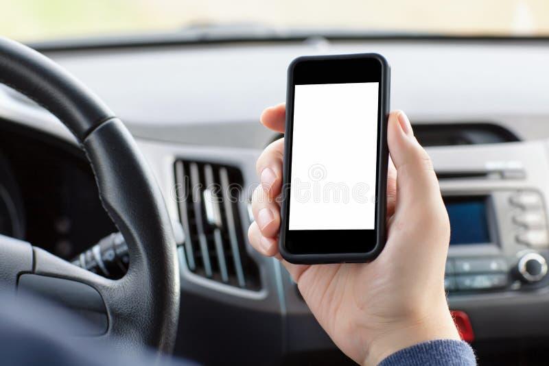 Man sammanträde i bilen och innehavet en telefon royaltyfri bild