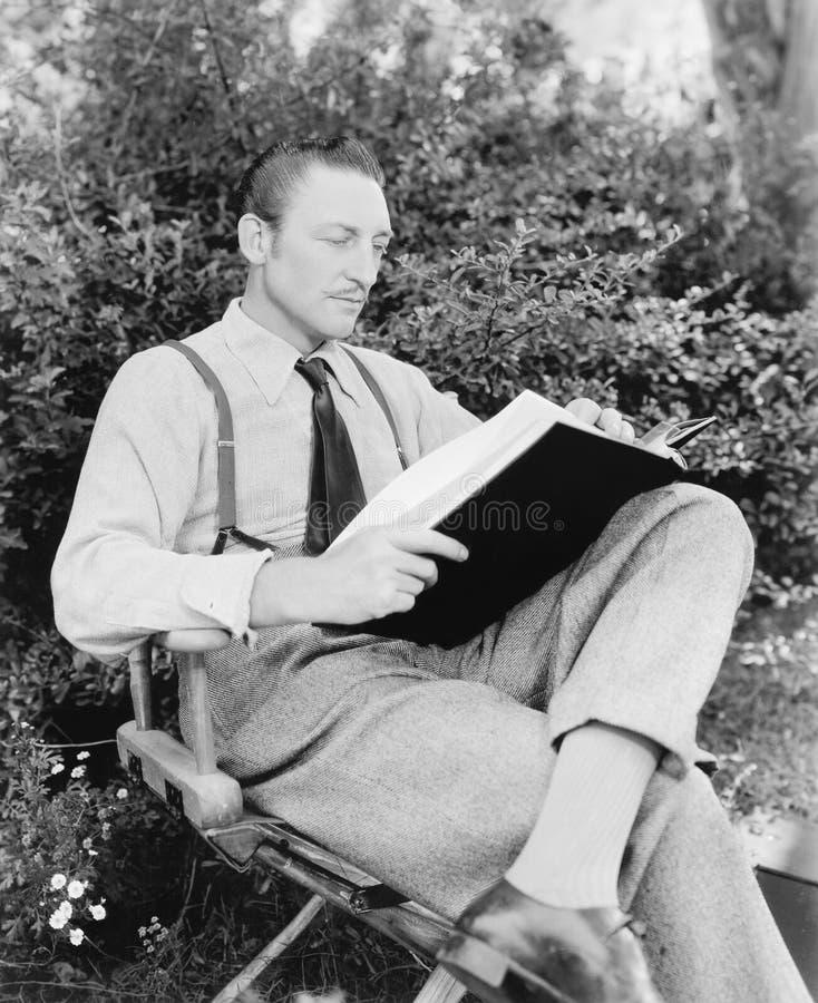 Man sammanträde i hans trädgårds- läsning en bok (alla visade personer inte är längre uppehälle, och inget gods finns Leverantörg royaltyfri foto