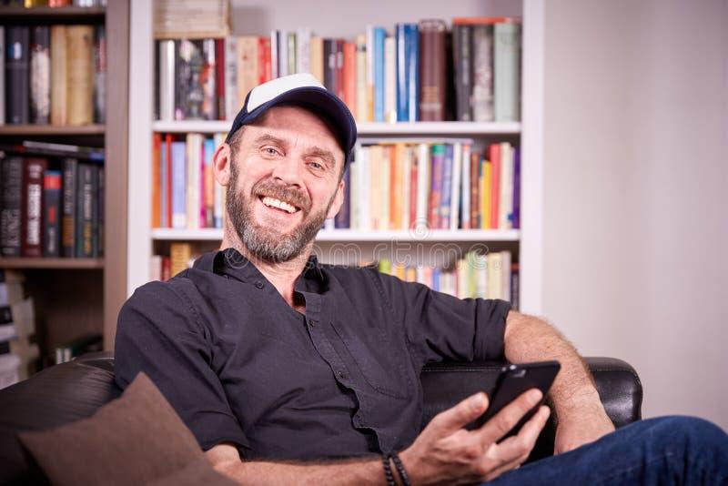 Man sammanträde i hans vardagsrum med att skratta för mobiltelefon royaltyfri foto