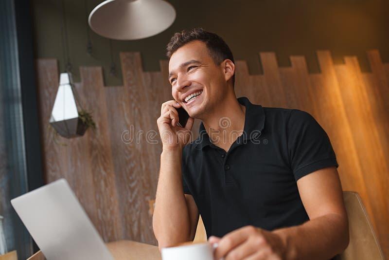 Man sammanträde i kafé med telefonen, bärbara datorn och kaffe royaltyfria bilder