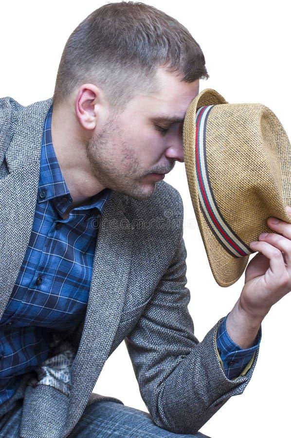 Man sammanträde med ögon som stängs och täckas hans framsida med hatten arkivfoto