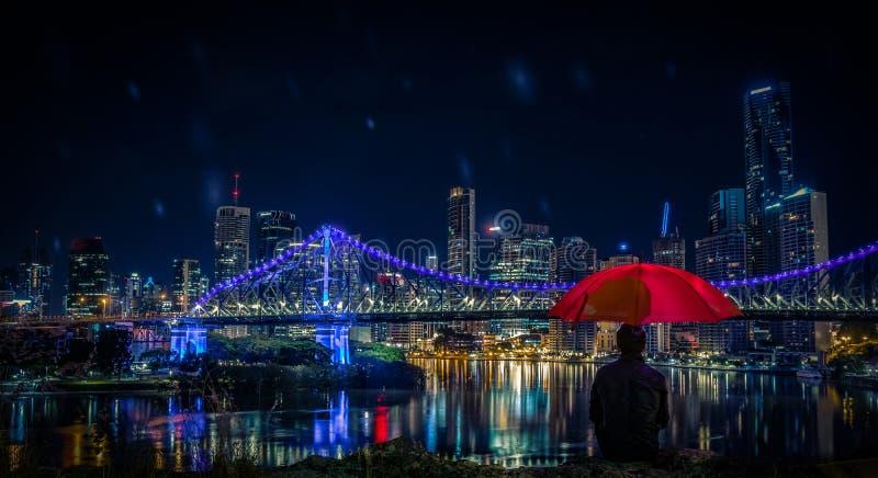 Man sammanträde med paraplyet och att se till moderna Brisbane arkivbilder