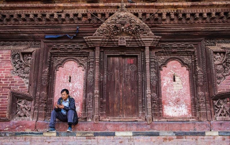 Man sammanträde nära väggen av den traditionella nepalesiska templet royaltyfria foton