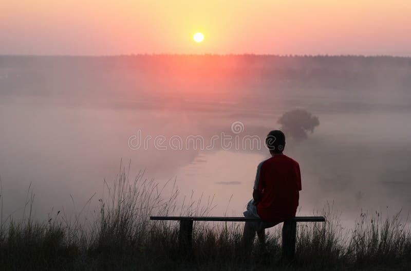 Man sammanträde på bänk och hållande ögonen på dimmig soluppgång arkivfoto