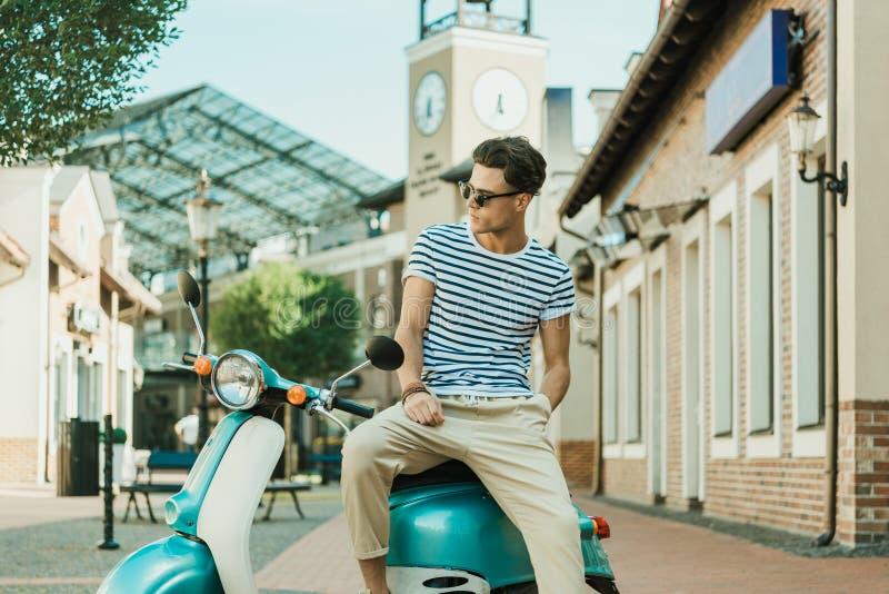 Man sammanträde på den retro sparkcykeln som parkeras på gatan arkivfoto