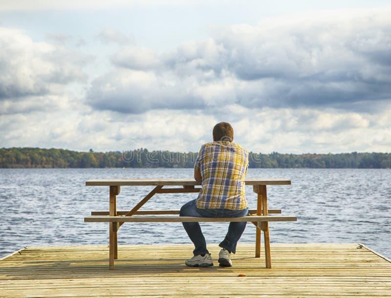 Man sammanträde på en bänk framme av en sjö royaltyfri bild