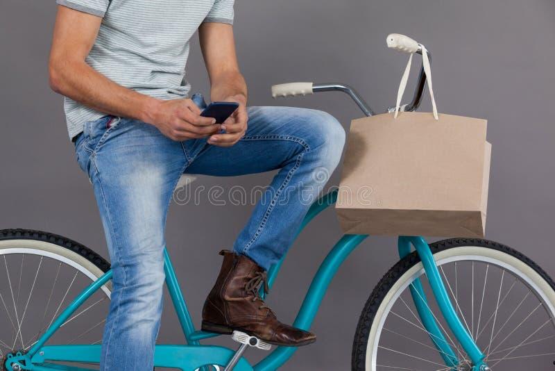 Man sammanträde på en cykel och användamobiltelefonen fotografering för bildbyråer