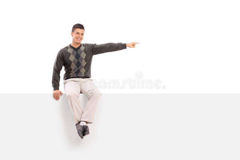 Man sammanträde på en skylt och att peka med hans hand arkivfoton