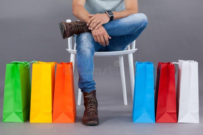 Man sammanträde på en stol med färgrika shoppingpåsar arkivbild