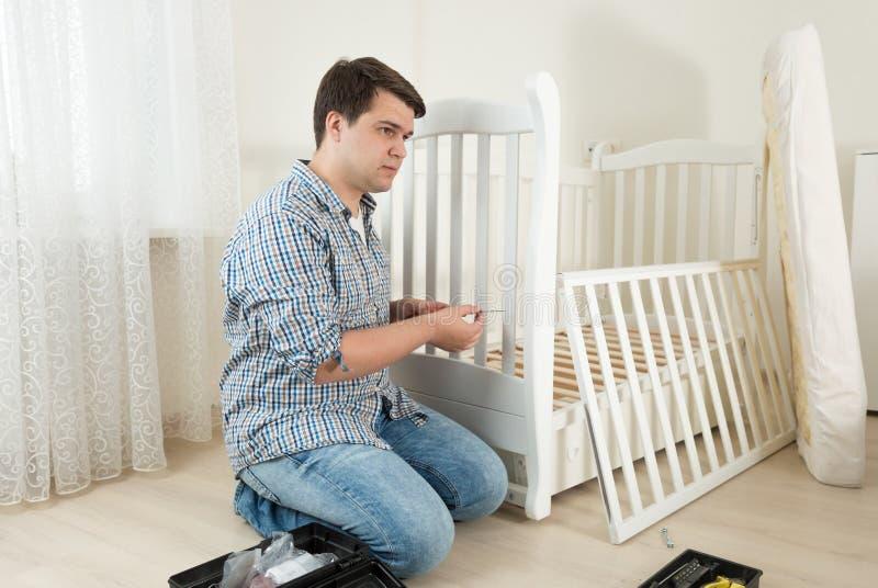 Man sammanträde på golv och att reparera säng för barn` s i barnkammare royaltyfria foton