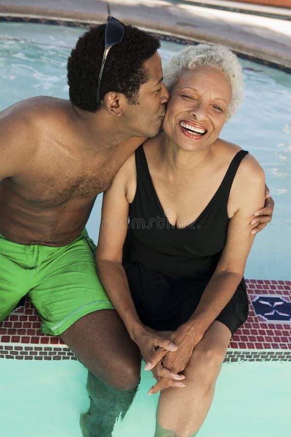 Man sammanträde på kanten av den kyssande modern för simbassängen på kinden höjd sikt. royaltyfri fotografi