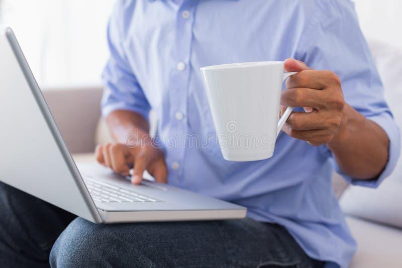 Man sammanträde på soffan genom att använda bärbara datorn som har kaffe royaltyfri bild