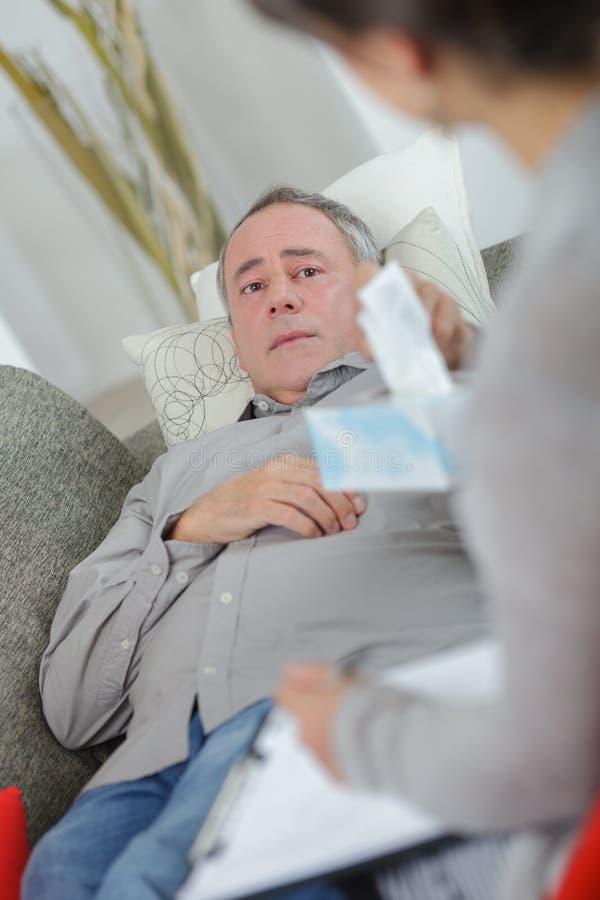 Man sammanträde på soffan och samtal till psykologen royaltyfria foton