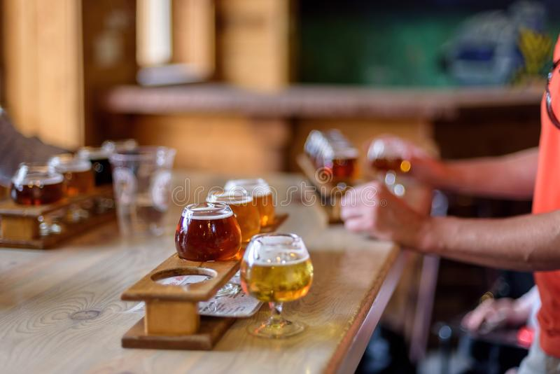 Beer flights lined up on a table at a microbrewery. Man sampling variety of different types of beers at a tasting room stock photos
