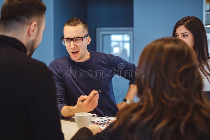 Man samtal aggressively på kontoret som möter till hans kollegor arkivbilder