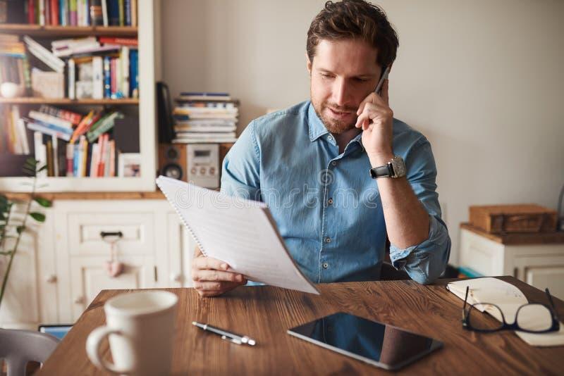 Man samtal på en mobiltelefon, medan läsa skrivbordsarbete hemma royaltyfria foton