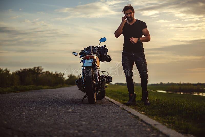 Man samtal på telefonen med hans cykel royaltyfri fotografi