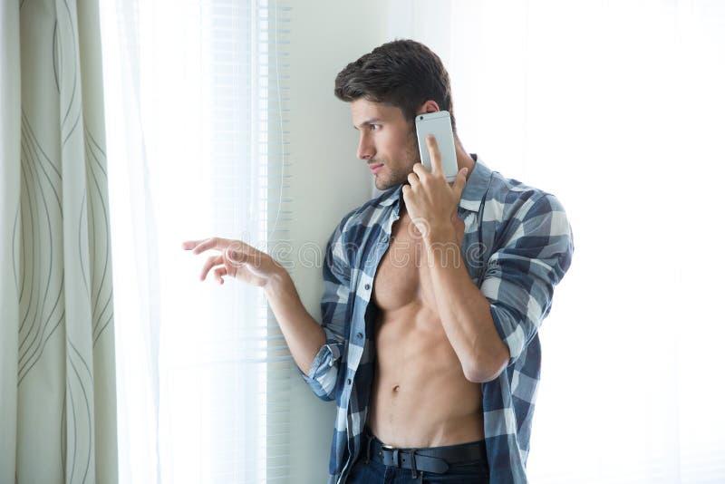 Man samtal på telefonen och att se i fönster arkivfoto