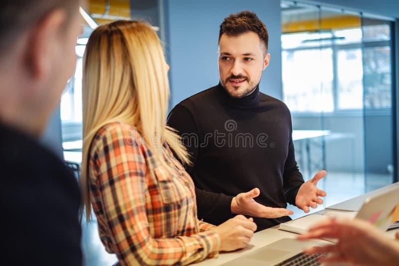 Man samtal till hans kvinnliga kollega på kontoret royaltyfria bilder