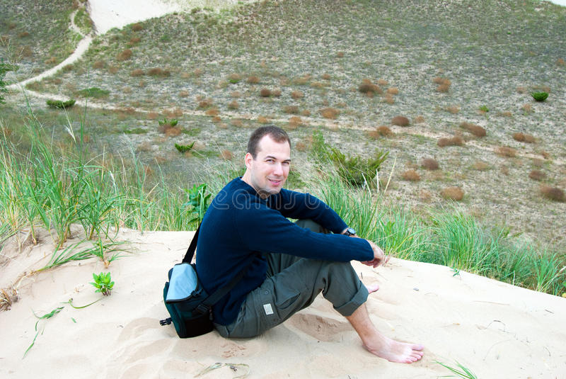 Man in sand dunes. Man sitting on the sand dunes enjoying nature and outdoors. relaxing and taking a break from hiking. shoes off resting royalty free stock photo