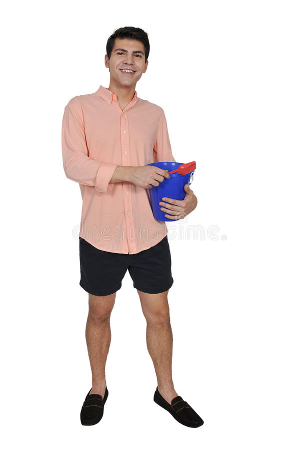 Man with a sand pail. Handsome young man holding a sand pail and a toy shovel stock photo