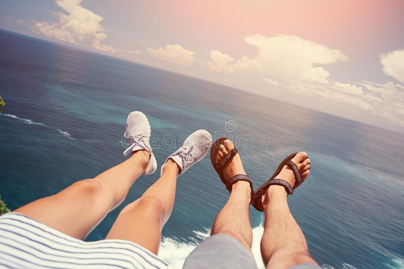 Man in sandals and woman in sport shoes sitting above the sea stock image