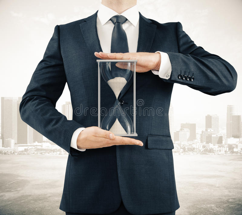 Man with sandglass in the hands on the city background,. Businessman with sandglass in the hands on the city background, time concept stock photos