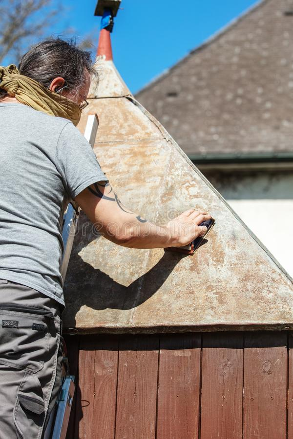 Man sanding the tin roof of his backyard shed with a sanding block. Removing rust and dirt royalty free stock photo