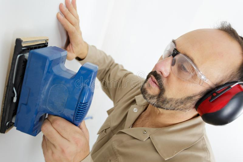 Man sanding wall. A man sanding a wall royalty free stock image