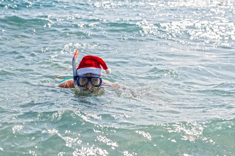Man in a Santa Claus hat and diving mask, Christmas background with copy space. Relax in tropical countries in the winter, New royalty free stock image