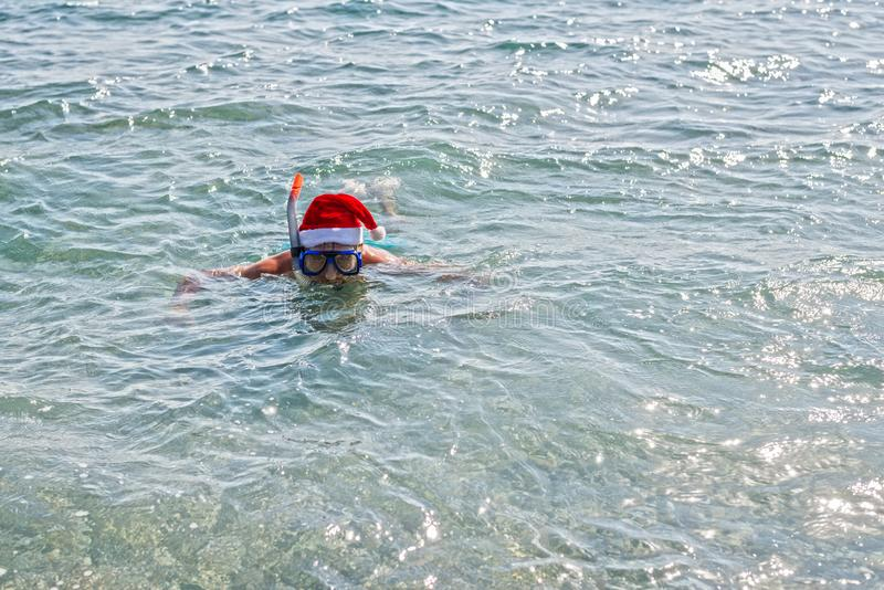Man in a Santa Claus hat and diving mask, Christmas background with copy space. Relax in tropical countries in the winter, New royalty free stock photography