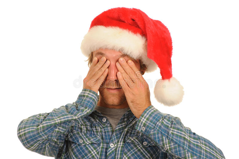 Man in Santa hat covering eyes. Young man in Santa hat covering eyes; isolated on white background stock photography