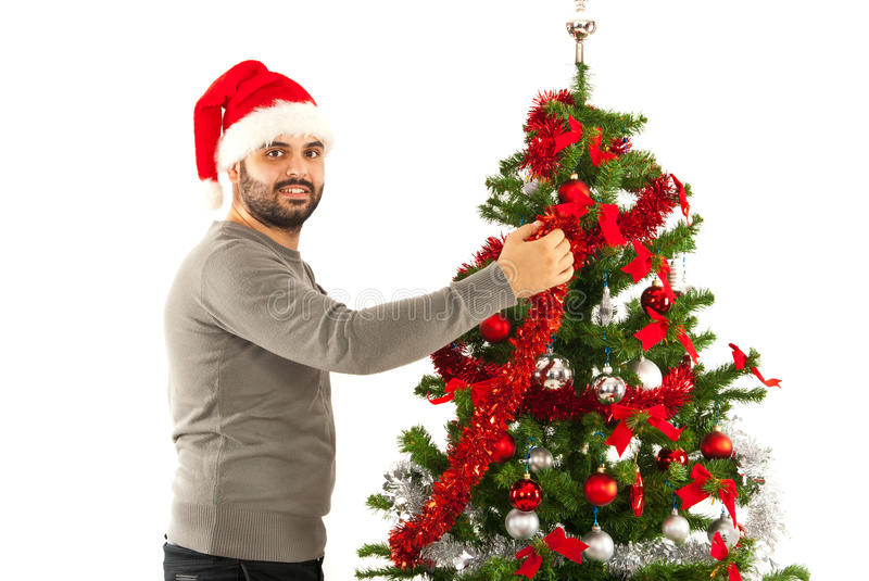 Man with santa hat decorate tree. Man with Santa hat decorate Christmas tree royalty free stock image