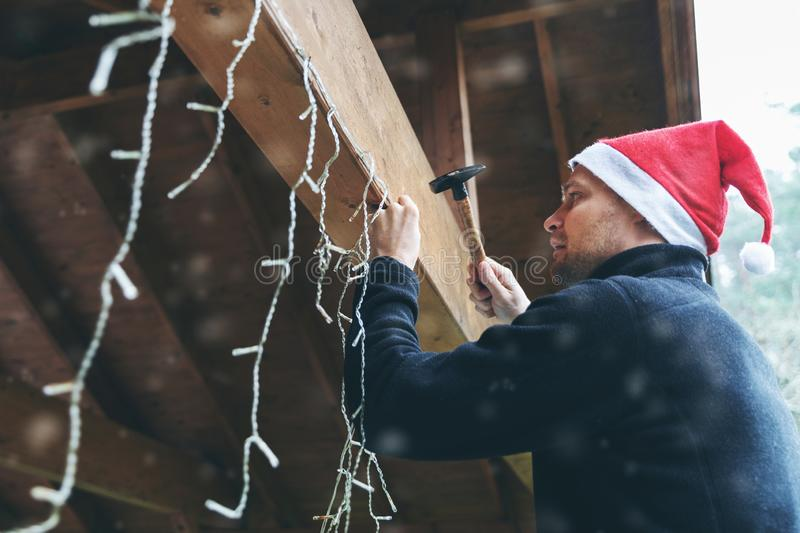 Man with santa hat decorating house outdoor carport with christmas string lights stock photo