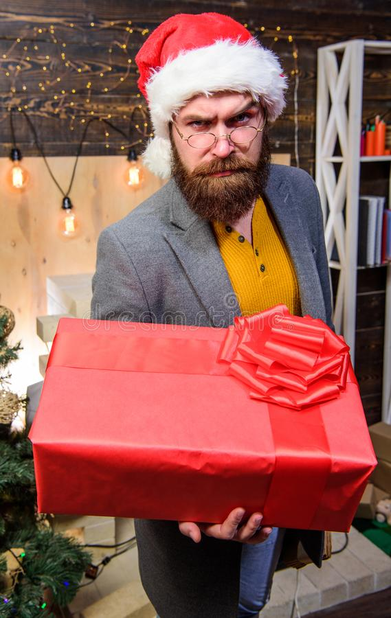 Man santa hat deliver gift. Spread happiness and joy. Bearded guy with eyeglasses carry present box. Delivery christmas stock photography