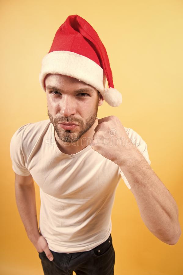 Man in santa hat with fist hand on orange background. Power, strength concept. Christmas and new year party. Winter holidays celebration royalty free stock photos