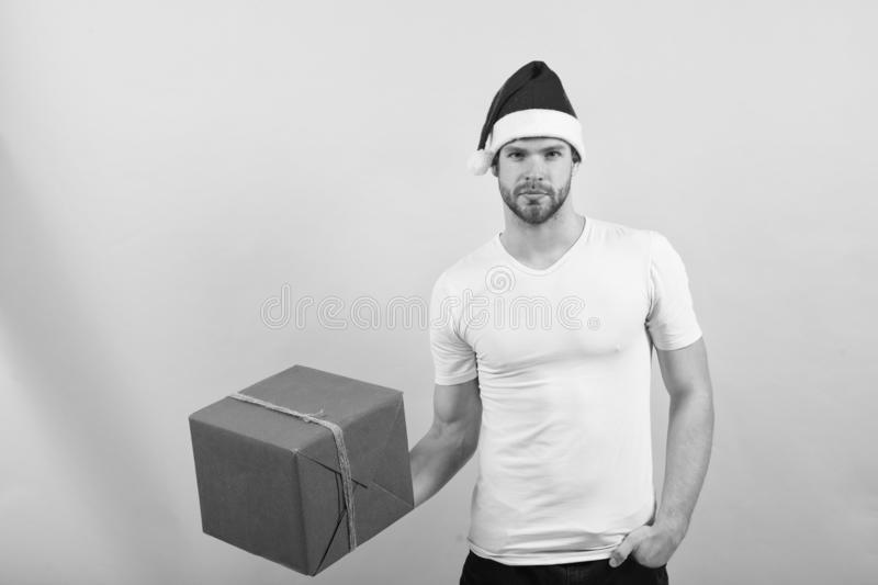 Man in santa hat hold christmas present. The morning before Xmas. happy santa man on yellow background. delivery stock photos
